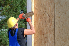 Builder hammering on a wooden wall panel Royalty Free Stock Photos