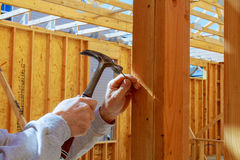 Builder hammers a nail into a wooden beam Stock Photography