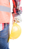 Builder hand holding helmet near leg Stock Images