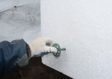 Builder hand installing rigid styrofoam insulation board with plastic nail, holder. Close up stock image