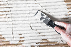 Builder hand with spatula spread white plaster Stock Photo