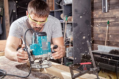Builder handles a wooden plank with a milling machine Royalty Free Stock Image