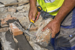 Builder hands with old clay brick and hammer Royalty Free Stock Image