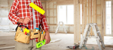 Builder handyman with paint roller. Builder handyman with construction tools in a new house background stock photography