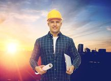 Builder in hard hat with blueprint and clipboard. Construction, building and people concept - male builder or foreman in yellow hard hat with blueprint and Stock Photo