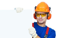 Builder in hard hat, earmuffs and goggles. Young builder in safety equipmant goggles hard hat earmuffs isolated with white empty billboard Stock Photo
