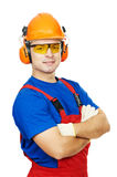 Builder in hard hat, earmuffs and goggles. Portrait of young builder in protective safety equipmant goggles hard hat earmuffs isolated Royalty Free Stock Photography