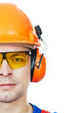 Builder in hard hat, earmuffs and goggles. Close-up Portrait of young builder in protective safety equipmant goggles hard hat earmuffs isolated Royalty Free Stock Photography