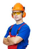 Builder in hard hat, earmuffs and goggles. Portrait of young builder in protective safety equipment goggles hard hat earmuffs isolated Royalty Free Stock Image