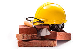 Builder. Hard hat, goggles, trowel, red brick building on a white background Stock Photography