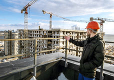 Builder in hard hat stands amid construction sites Stock Photography