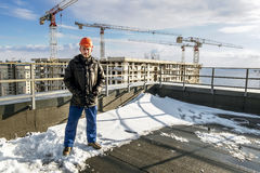 Builder in hard hat stands amid construction sites Royalty Free Stock Photos