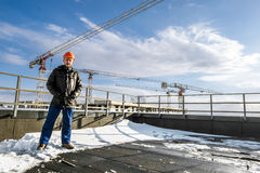 Builder in hard hat stands amid construction sites Stock Images