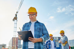 Builder in hardhat with clipboard at construction Royalty Free Stock Photos