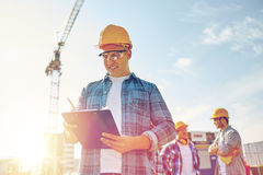 Builder in hardhat with clipboard at construction. Business, building, paperwork and people concept - happy builder in hardhat with clipboard and pencil over Royalty Free Stock Photography