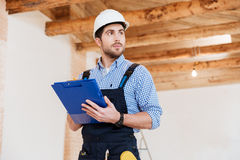 Builder in hardhat with clipboard and pencil indoors Stock Photos