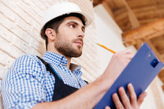 Builder in hardhat with clipboard and pencil indoors. Pensive builder in hardhat with clipboard and pencil indoors Royalty Free Stock Photos