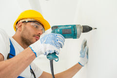 Builder in hardhat with drill perforating wall Stock Photography