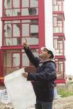 Builder in helmet with blueprint on building site Stock Photo