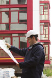Builder in helmet with blueprint on building site Stock Photography