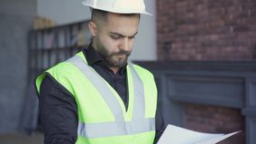 Builder in the helmet and green jacket examining drawings. Professional at work. Man looking through papers. Builder in the helmet and green jacket examining stock footage