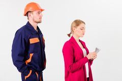 Builder looks at woman with busy face counting money,. Builder in helmet looks at women with busy face counting money, isolated on white background. Repairer royalty free stock photography