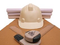 Builder Helmet Paper Rolls Ruler. White colored Builder Safety Helmet with paper rolls & ruler on brown paper royalty free stock photos