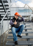 Builder in helmet sitting on metal staircase and showing thumb u Royalty Free Stock Photo