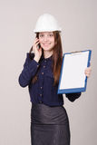 Builder in helmet talking but phone with a folder hands Royalty Free Stock Photo