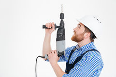 Builder in helmet using drill and looking up Royalty Free Stock Photo