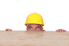 Builder hiding behind a table. Scared builder hiding behind a table Royalty Free Stock Images