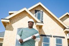 A builder holding a blueprint Stock Photos