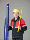 Builder holding a ladder and a level Royalty Free Stock Photo