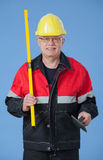 Builder holding a level and a trowel Royalty Free Stock Photos