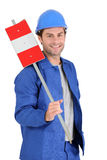 Builder holding road sign. Royalty Free Stock Image
