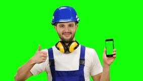 Builder holds a phone in his hands and shows a thumbs up. Green screen. Mock up. Builder in a suit and a helmet holds the phone in his hands and shows a thumbs stock footage