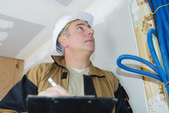Builder inspection checking electrics. Builder inspection checking the electrics stock photo