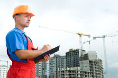 Builder inspector at construction. One builder worker with clipboard inspecting works at construction site Stock Photos