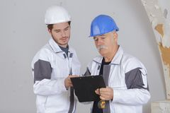 Builder and inspector looking at unfinished property. Builder and inspector looking at an unfinished property Royalty Free Stock Image
