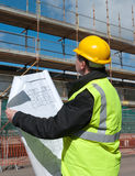 Builder inspects construction site. Architect, foreman or engineer at work on a building site. He inspects the site while looking at the plans for the Stock Image
