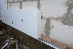 Builder installing anchors in house wall for rigid insulation foam. Close up royalty free stock photo