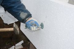 Builder installing rigid styrofoam insulation board for energy s. Aving. Rigid extruded polystyrene insulation with plastic nails and hammer stock photos