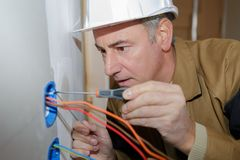 Builder installing silver wall-mounted ac power socket with screwdriver. Builder installing a silver wall-mounted ac power socket with screwdriver Royalty Free Stock Photography
