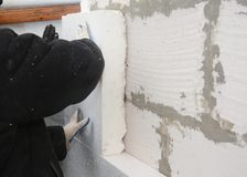 Builder installing rigid styrofoam insulation board for energy saving. Rigid extruded polystyrene insulation. Builder installing  styrofoam insulation board for Stock Image