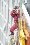 Builder joiner installing glass window on building. Worker builder installing glass windows on facade of business building Stock Photo