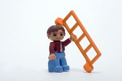 Builder with a ladder. Plastic worker holds a plastic ladder Royalty Free Stock Photo
