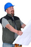 Builder laughing at plans Royalty Free Stock Photo