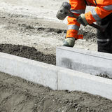 Builder laying bricks. Close up of builder holding mallet laying breeze block bricks in cement Stock Photo