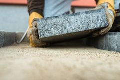 Builder laying a paving brick placing it on the sand foundation Royalty Free Stock Photo