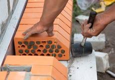 Builder lays bricks in cement mortar Stock Photos